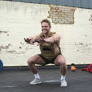 strong athlete doing squats to exercise his legs' muscles