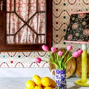 counter with colorful wallpaper, cabinets, and flowers
