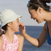 mother applying sunscreen to daughter's nose