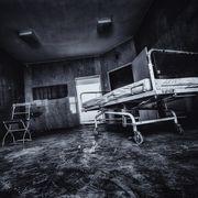 creepy abandoned hospital photo of surgery table