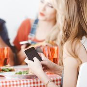 Teenage girl using smart phone during lunch with family