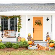 front porch with swing and orange door decorated for fall