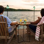 couple sitting next to lake with glass tiki torches