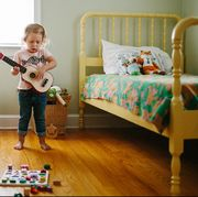 toddler playing guitar in bedroom with two yellow beds