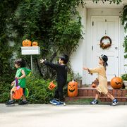 kids walking past an ivy covered house in halloween costumes