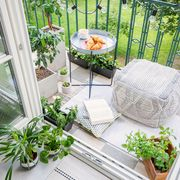 Top view of a balcony with plants, pouf a table with breakfast