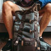 man packing travel backpack in bedroom