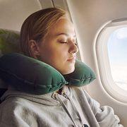 woman using green travel pillow