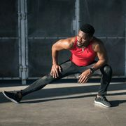 Urban athlete exercising and stretching legs