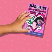 kid's hands with mad libs and heart shaped box