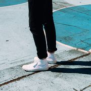 man in white sneakers standing on outdoor basketball court