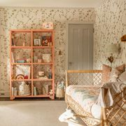 nursery, floral wallpaper, green curtains, day bed, peach bookshelf, rocking chair, children's toys