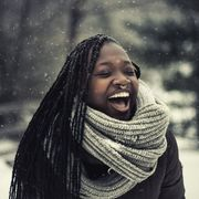 winter quotes young woman laughing while it's snowing outside