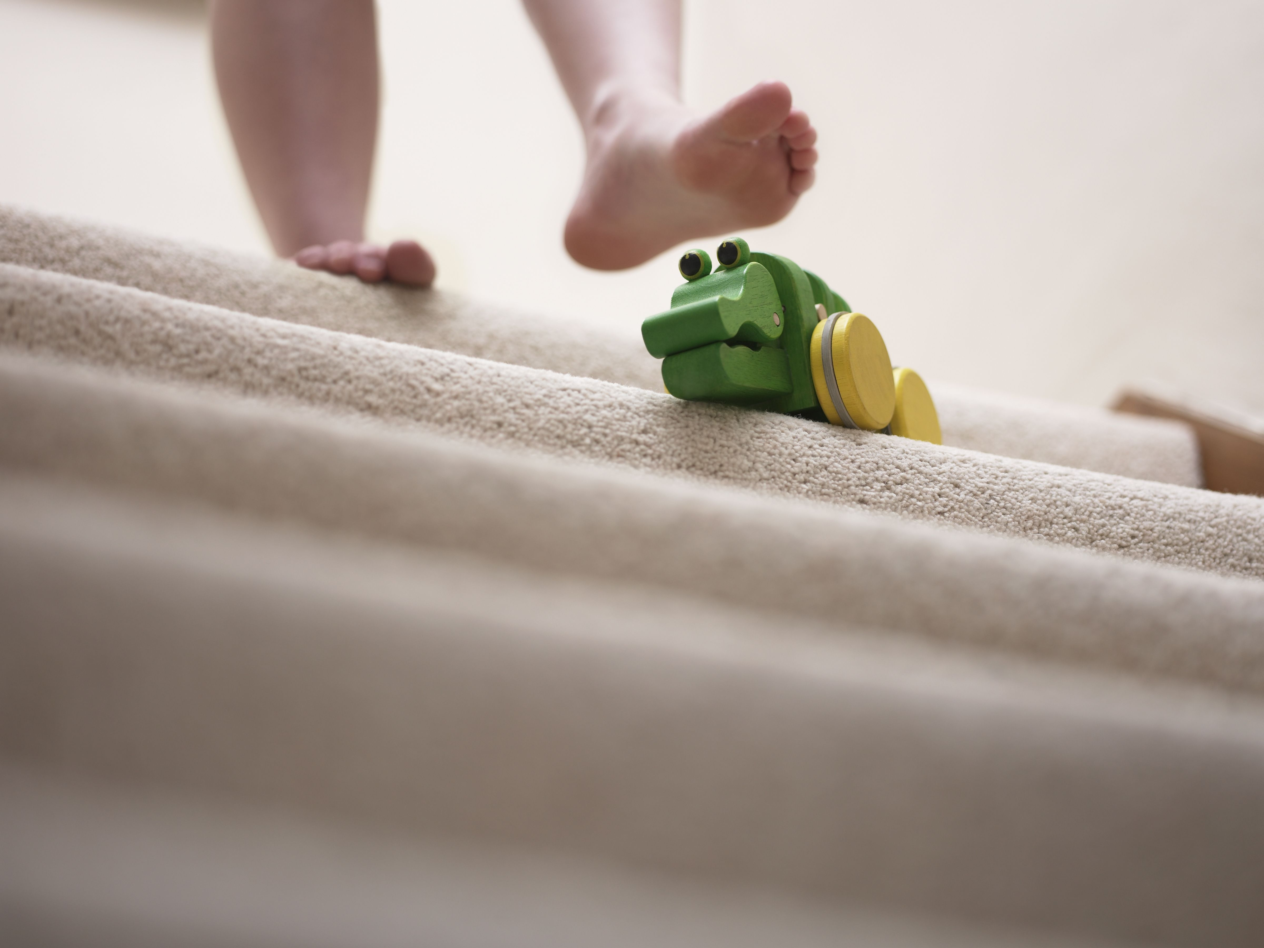 Woman about to slip on toy left on staircase