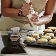 woman icing cupcakes at kitchen counter