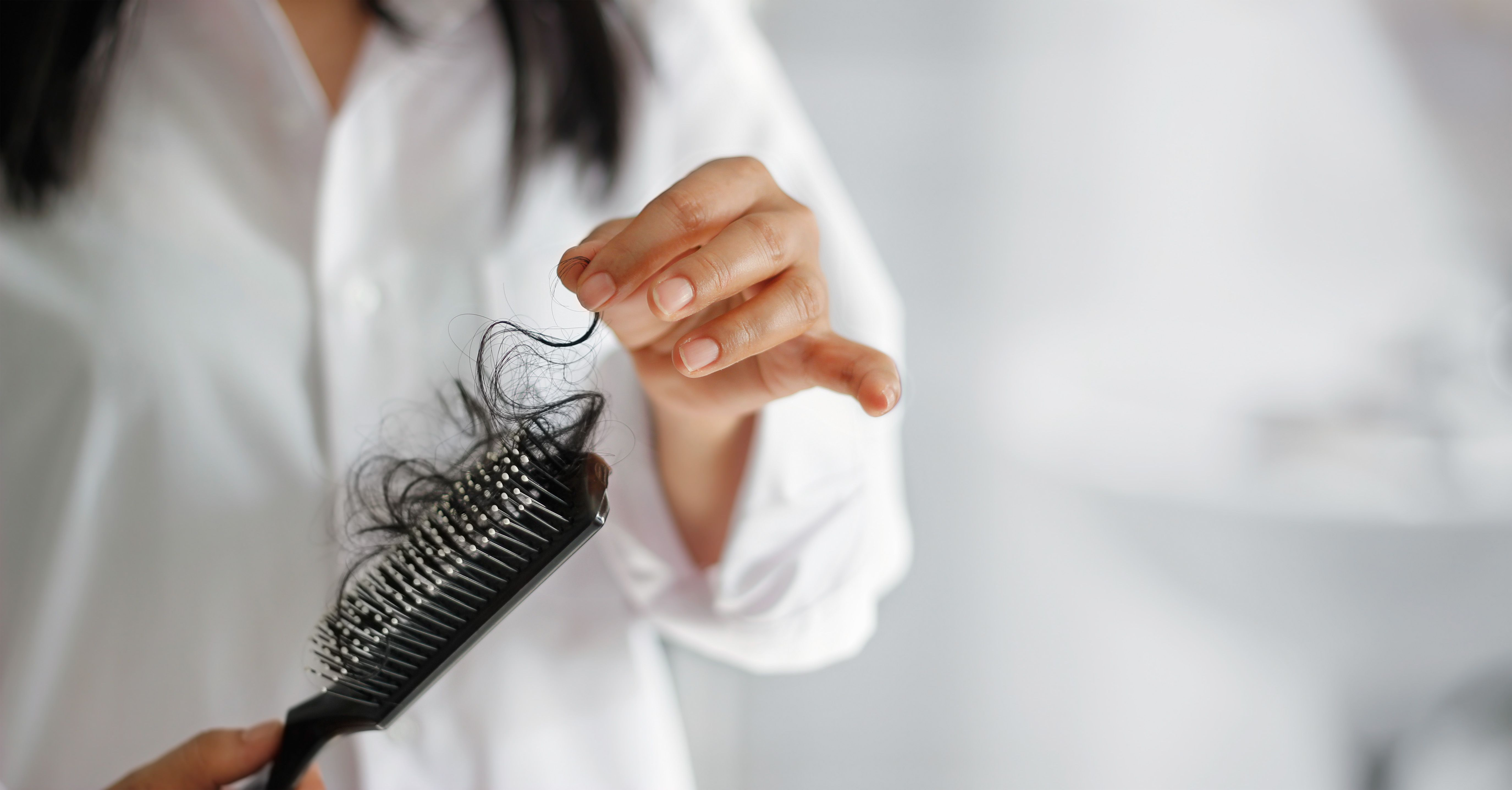 woman losing hair on hairbrush in hand on bathroom background