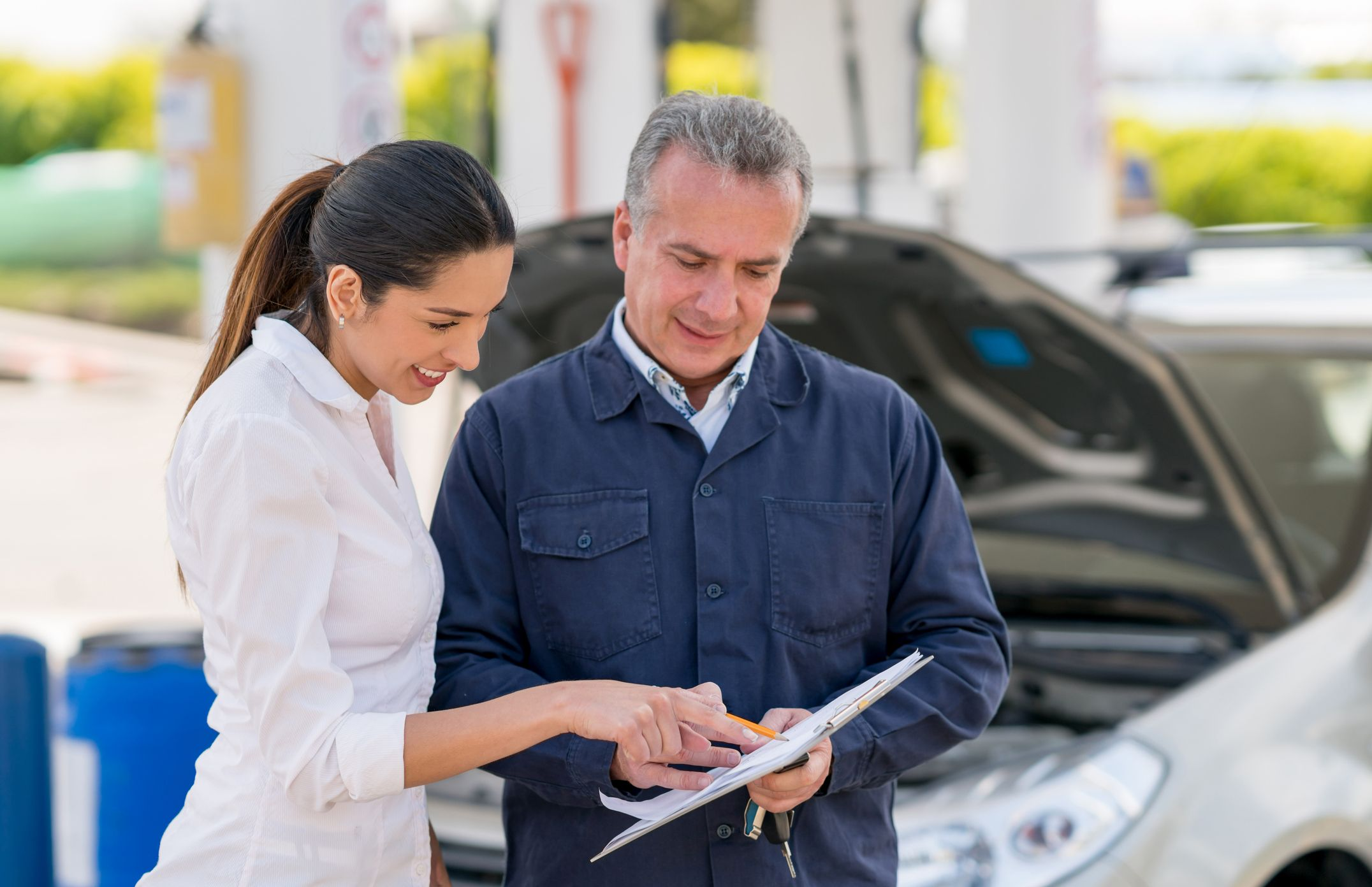 Woman talking to a mechanic about her car royalty free image 1591276804