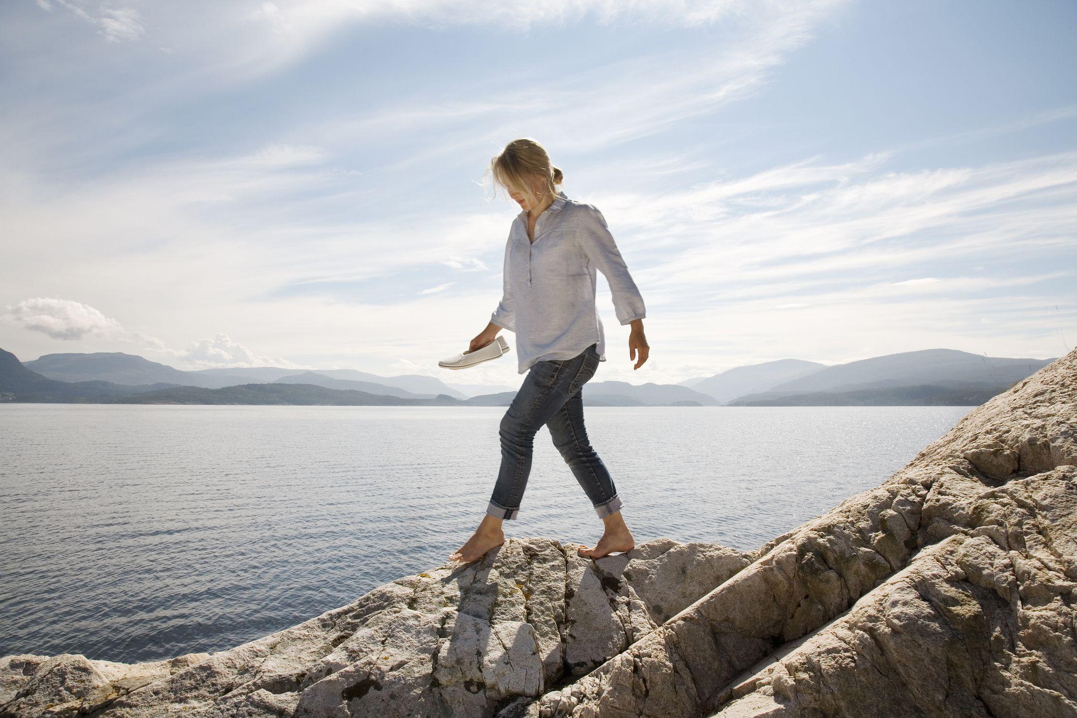 Woman walking on rocky beach by sea
