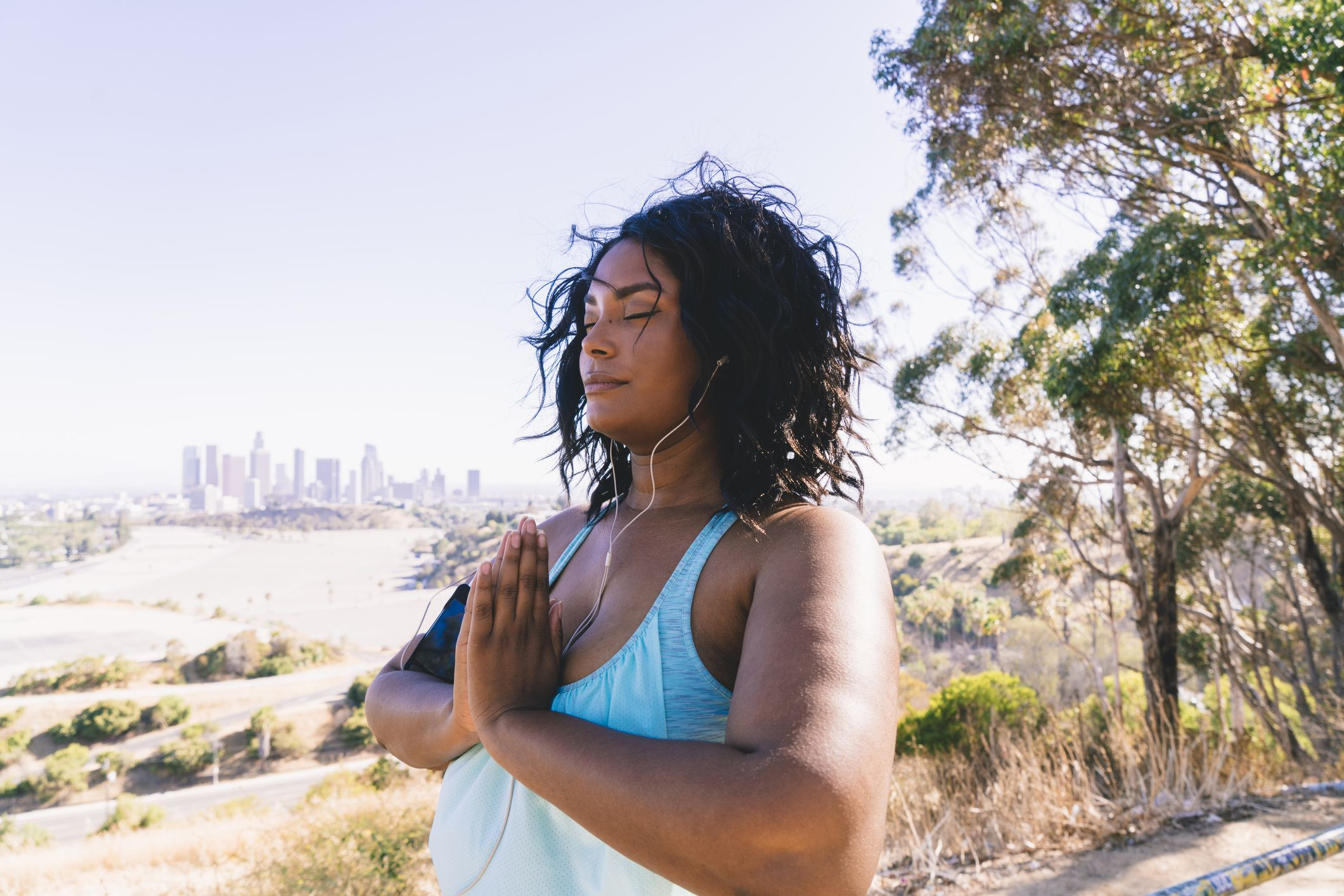 Woman with eyes closed doing prayer position exercise against clear sky