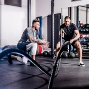 Young Adult Man Swinging Ropes While Fitness Instructor Motivates Him
