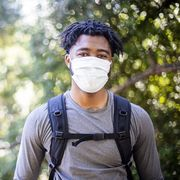 young black man wearing a face mask while hiking
