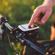 A young brunette guy on a mountain bike uses a cycling computer, a navigator in the field sunset of the day