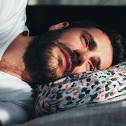 young depressed man crying in bed