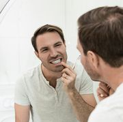 young man brushing teeth in the bathroom