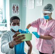 young man taking a selfie while getting vaccinated