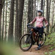 a young pregnant woman mountain bikes on a trail in the forest of oregon