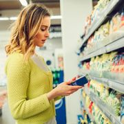 young woman groceries shopping in local supermarket