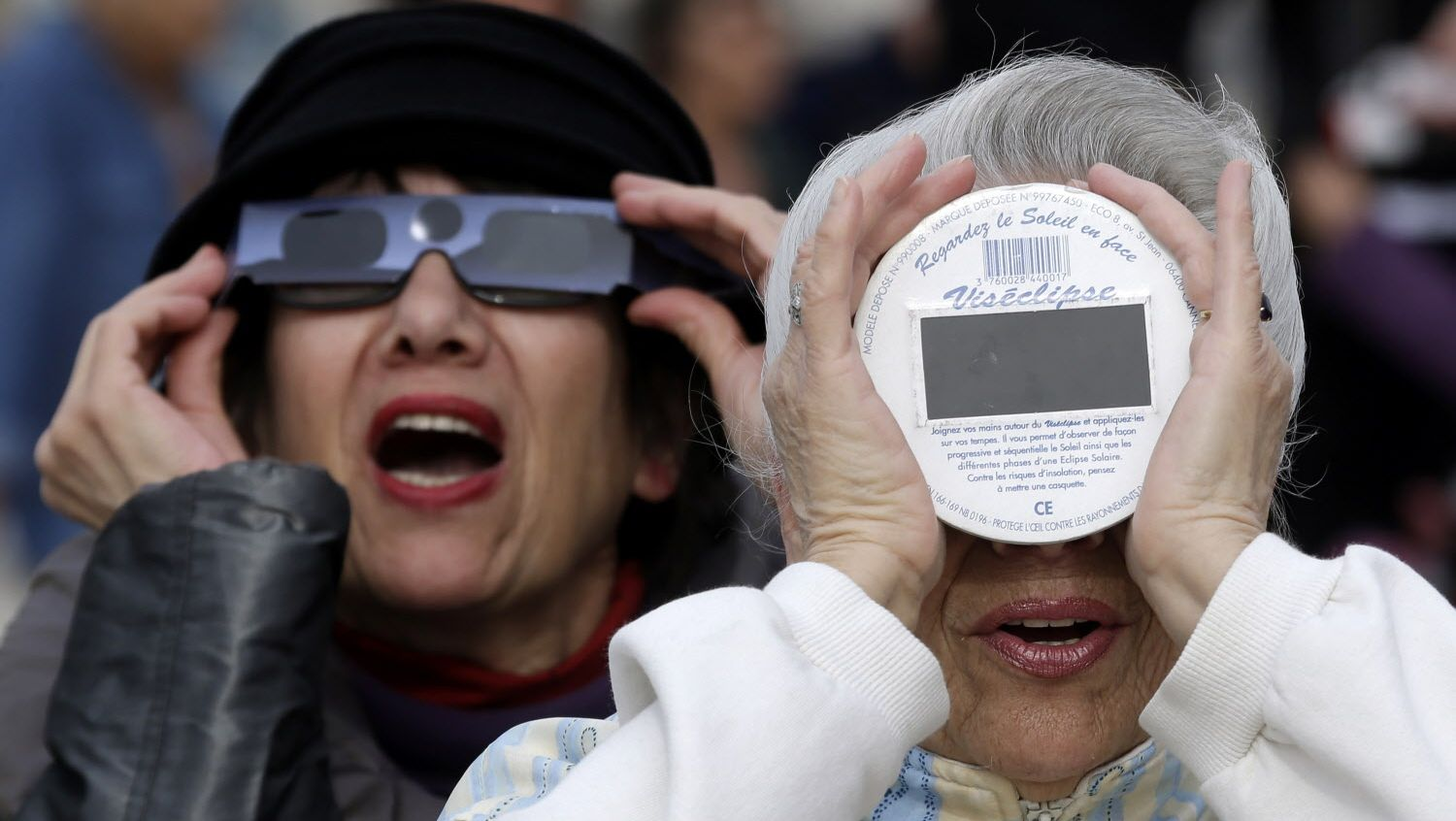 People look at a solar eclipse in the sky of Nice, southeastern France, Friday, March 20, 2015.  (AP Photo/Lionel Cironneau)