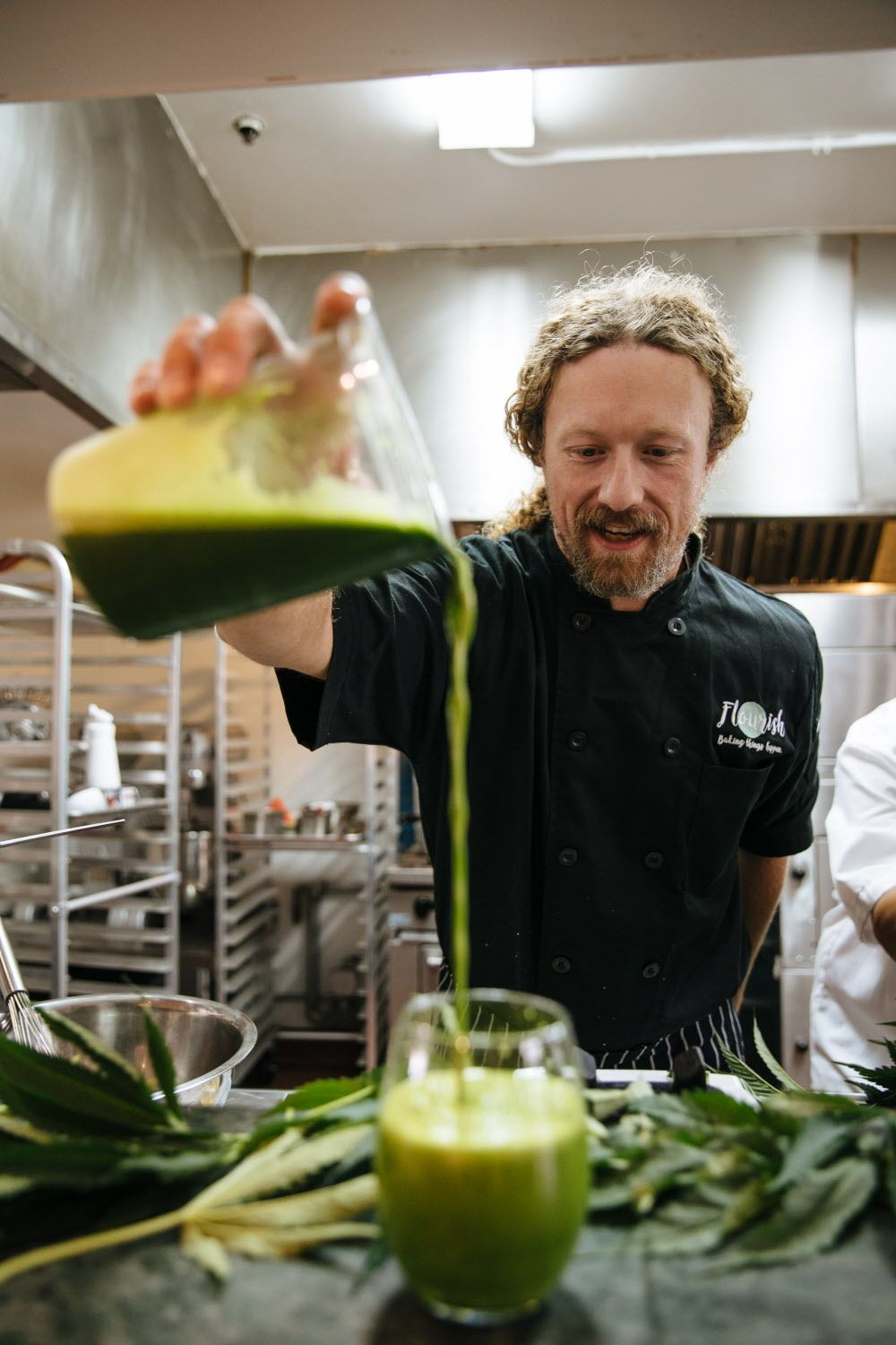 Payton Curry, Founder of Flourish Cannabis, pours freshly  juiced marijuana leaves at his kitchen in San Francisco, Calif. Tuesday, August 8, 2017.
