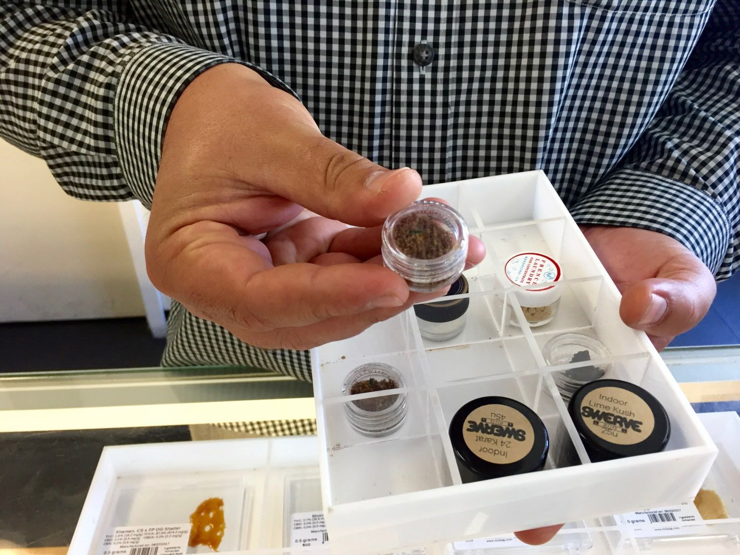 "Victor Pinho, Director of Marketing and Communications at Berkeley Patients Group, a dispensary in Berkeley, Calif., holds a container of bubble hash on July 24th, 2017. When Berkeley's first set of cannabis contaminant regulations went into effect, the bubble hash market ""fell apart,"" said Pinho."