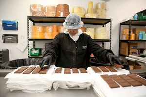 Production assistant and chocolatier Juana prepares mint irish cream milk chocolate bars for packaging at Kiva's chocolate factory on Friday, August 11, 2017, in Oakland, Calif.