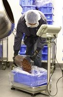 Panning technician II Train Ford measures chocolate in bins after doing quality checks on Terra Bites 120mg Chocolate Covered Blueberry Bites at Kiva's chocolate factory on Friday, August 11, 2017, in Oakland, Calif.