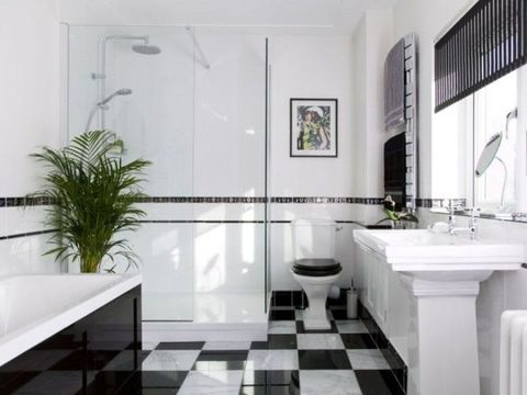 Hardwearing black and white glossy marble tiles set the tone for this art deco room