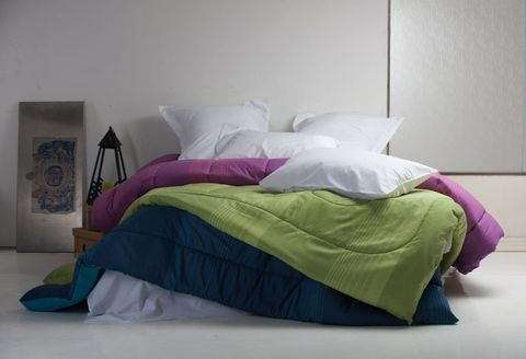 Unmade bed with coloured duvets and white pillowcases