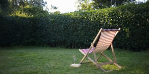 A single deck chair with a book and sparkling wine, set in a country garden.