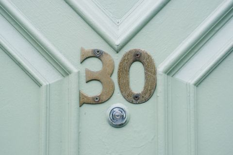 The number 30, in scratched gold coloured brass digits, is screwed into a pale mint green coloured panelled door at the entrance of an urban home in the Cotham area of Bristol, UK. Just beneath it, is the peephole used for security of the occupants.