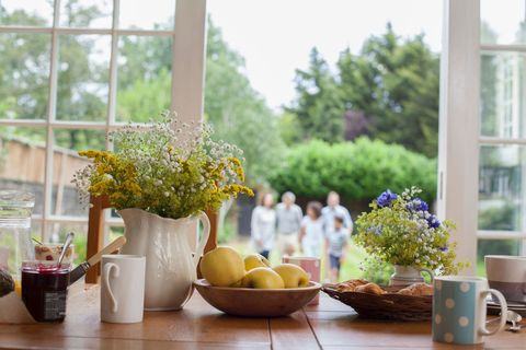 Kitchen table with breakfast foods, family in garden behind, focus on table