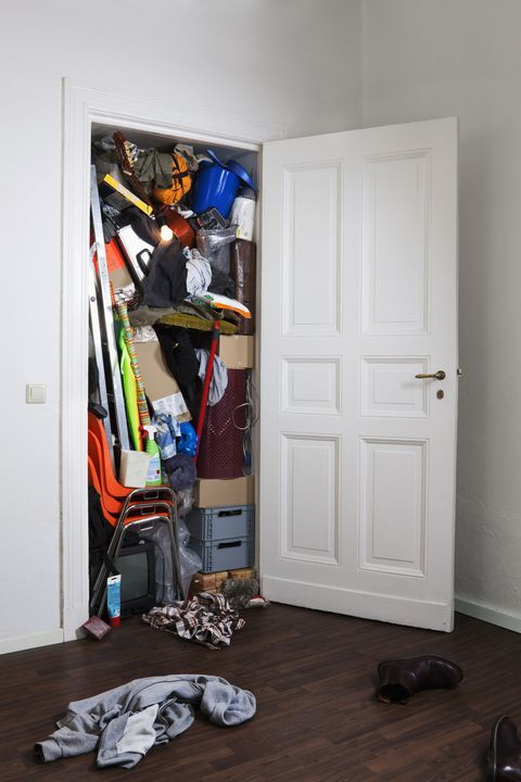 A cupboard stuffed with various storage items