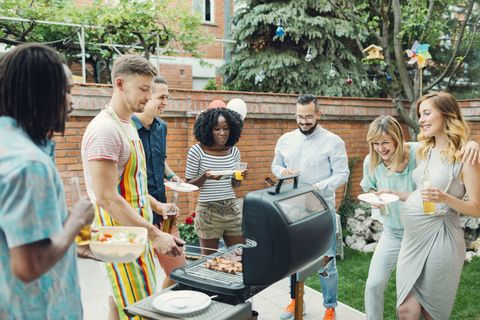 Group of young people eating at barbecue party in a backyard. Selective focus to man grilling and giving meals to his friends.