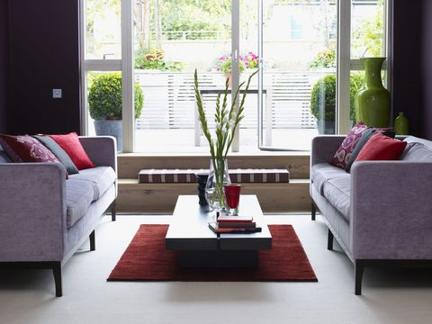 Vase of flowers and books on coffee table between matching sofas and cushions in lounge brightly lit by French windows