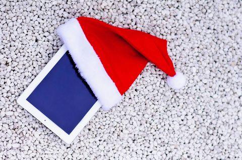 Digital tablet wearing Christmas hats