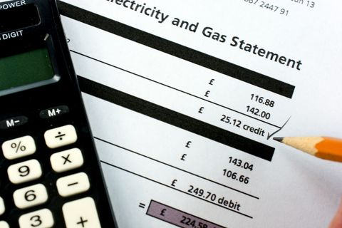 A close-up of a British residential utility statement with calculator and pencil.