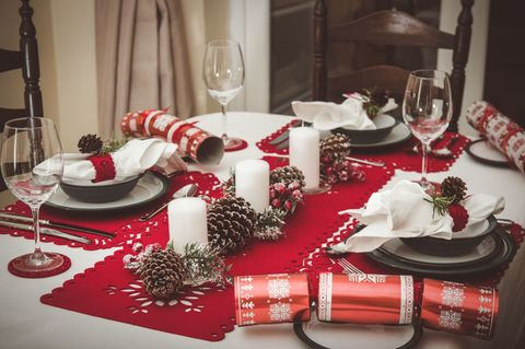 dining table set for christmas lunch with crockery glassware napkins and crackers