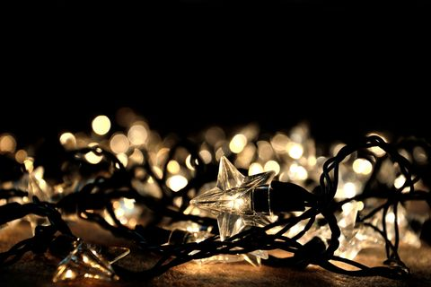a rope of tangled christmas fairy lights in the shape of stars are scattered on the