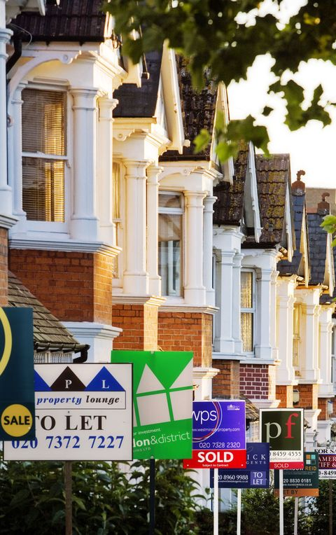 Row of houses with for sale signs in front of them