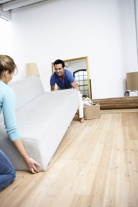 Couple lifting sofa indoors